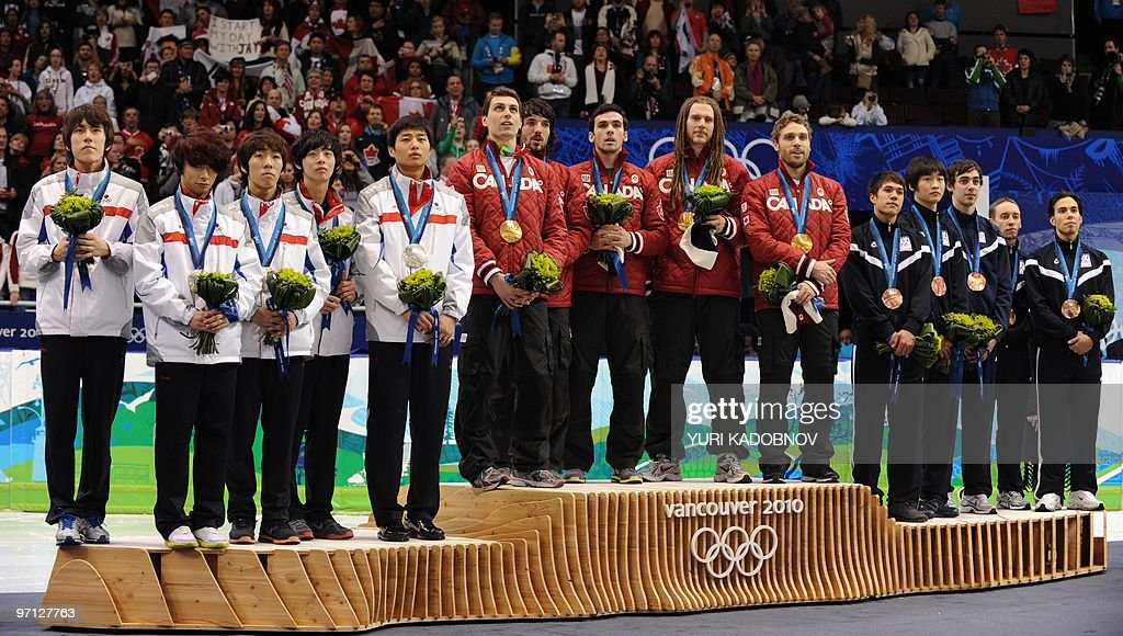 The gold medal-winning Canadian team (C) poses on the podium with silver medalist South Korea (L) and the bronze medal-winning team of the US during the victory ceremony of the men's 5,000m relay short-track final at the Pacific Coliseum in Vancouver during the 2010 Winter Olympics on February 26, 2010.