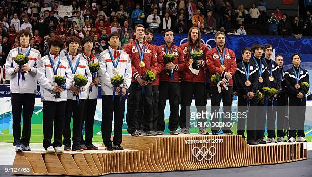 The gold medalwinning Canadian team poses on the podium with silver medalist South Korea and the bronze medalwinning team of the US during the...
