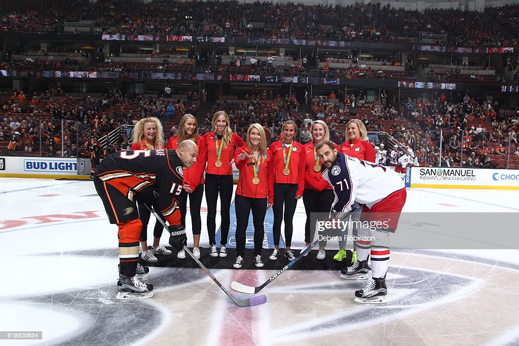 The gold medal-winning Team USA Women's Water Polo team participates in the ceremonial puck drop prior to the game between the Anaheim Ducks and the Columbus Blue Jackets on October 28, 2016 at Honda Center in Anaheim, California.