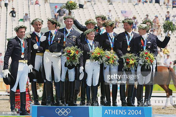 The gold, silver and bronze medal teams of the Germany, Spain and the United States share the podium during the medal ceremony in the team dressage...
