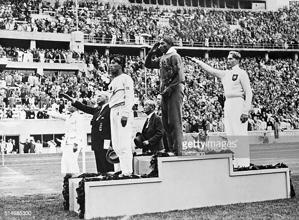 The gold silver and bronze medal winners in the long jump competition salute from the victory stand at the 1936 Summer Olympics in Berlin From left...