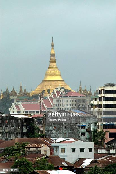 The golden bellshaped stupa of the Shwedagon Pagoda shines behind houses and buildings
