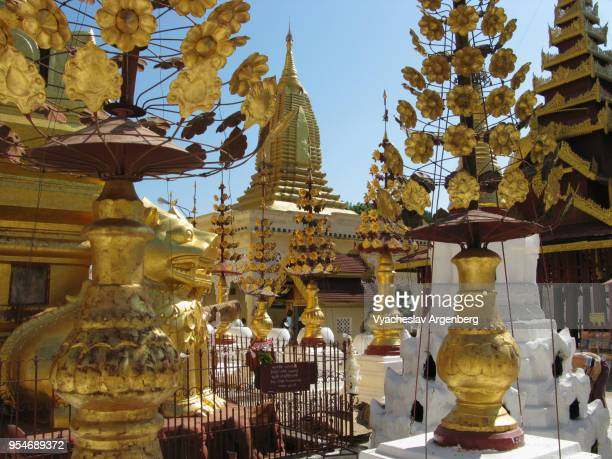 the golden buddhist bells and statues at shwezigon pagoda, bagan, myanmar - argenberg stock pictures, royalty-free photos & images