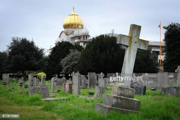 The golden dome of the Sri Guru Singh Sabha Sikh temple in Southall rises up behind the graves of Havelock cemetery on April 22 2017 in London...
