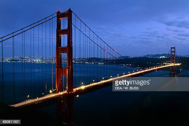 The Golden Gate Bridge 19331937 architect Joseph Baermann Strauss with the bay and the city of San Francisco in the background at night California...