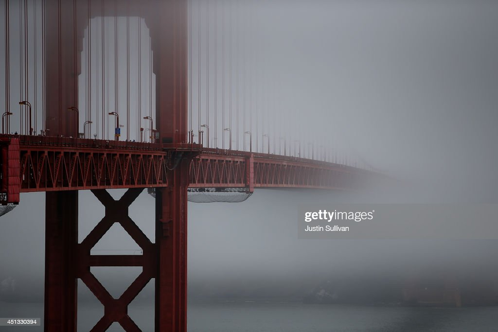 The Golden Gate Bridge peeks through the fog on June 27, 2014 in San Francisco, California. The Golden Gate Bridge district's board of directors voted unanimously to approve a $76 million funding package to build a net suicide barrier on the iconic span. Over 1,500 people committed suicide by jumping from the iconic bridge since it opened in 1937. 46 people jumped to their death in 2013.