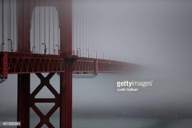 The Golden Gate Bridge peeks through the fog on June 27 2014 in San Francisco California The Golden Gate Bridge district's board of directors voted...