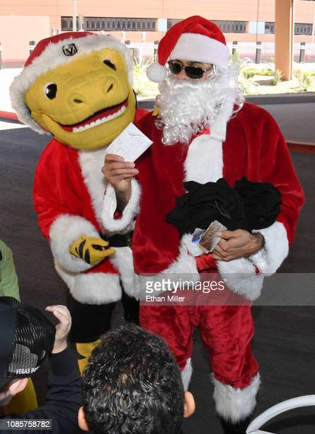 The Golden Knights mascot Chance the Golden Gila Monster and Ryan Reaves of the Golden Knights dressed as Santa Claus give out gifts to kids at...