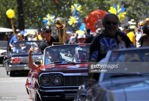 The Golden State Warriors' 2015 championship trophy is carried in a vintage car during the Golden State Warriors Victory Parade on June 12 2018 in...