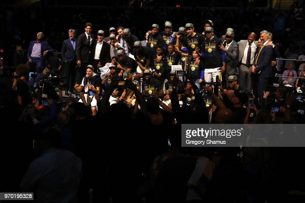The Golden State Warriors celebrate with the Larry O'Brien Trophy after defeating the Cleveland Cavaliers during Game Four of the 2018 NBA Finals at...