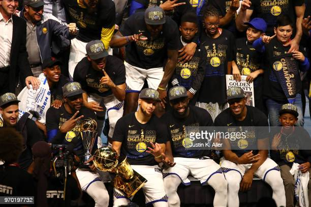The Golden State Warriors celebrate with the Larry O'Brien Trophy after defeating the Cleveland Cavaliers in Game Four of the 2018 NBA Finals at...