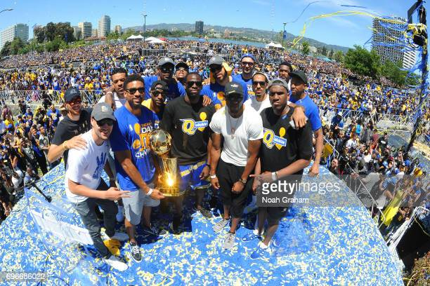 The Golden State Warriors hold up the Larry O'Brien Trophy during the Victory Parade and Rally on June 15 2017 in Oakland California at The Henry J...
