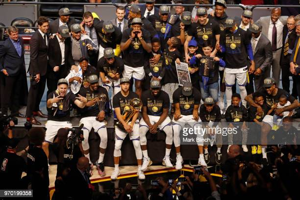 The Golden State Warriors pose for a group photo with the Larry O'Brien Championship Trophy after winning Game Four of the 2018 NBA Finals against...