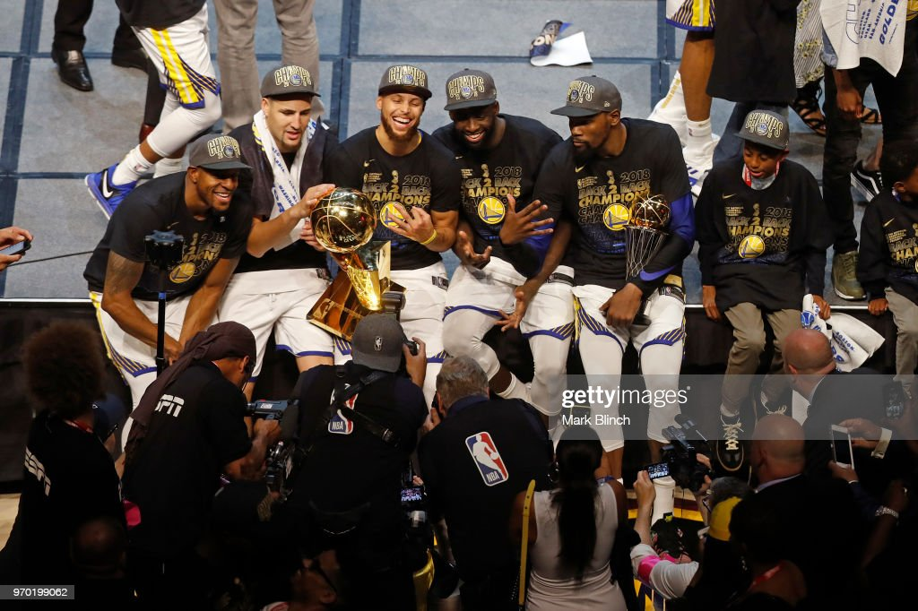 The Golden State Warriors pose for a photo on stage with the Larry O'Brien Championship Trophy after winning Game Four of the 2018 NBA Finals against the Cleveland Cavaliers on June 8, 2018 at Quicken Loans Arena in Cleveland, Ohio.