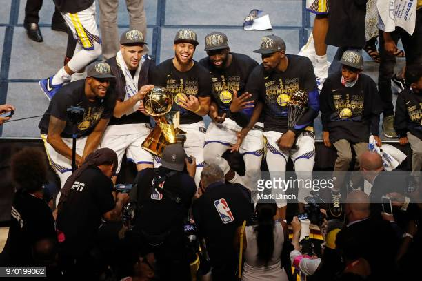 The Golden State Warriors pose for a photo on stage with the Larry O'Brien Championship Trophy after winning Game Four of the 2018 NBA Finals against...