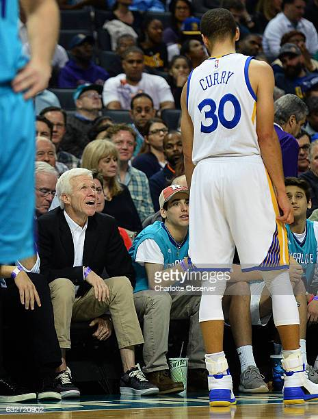 The Golden State Warriors' Steph Curry talks with Davidson College coach Bob McKillop left during a break in action against the Charlotte Hornets at...