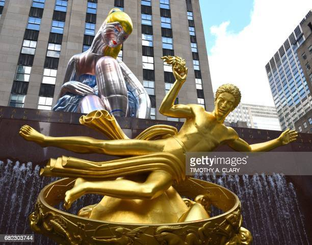 The golden statue of Prometheus sits in front of the public art exhibition of a 45foot tall inflatable nylon sculpture depicting a seated ballerina...