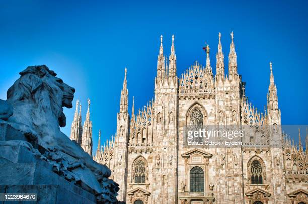 the golden sunshine is reflecting on the front of the magnificent duomo di milano or milan cathedral - cattedrale foto e immagini stock