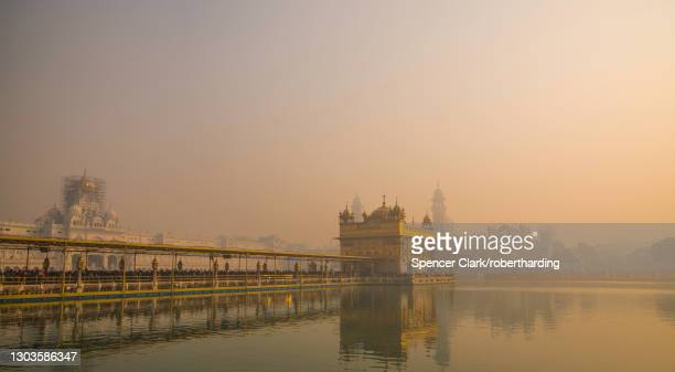 the golden temple at sunrise through fog, amritsar, punjab, india, asia - golden temple india stock pictures, royalty-free photos & images