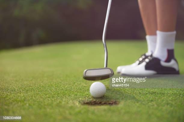the golf player is playing golf match by using a golf club hit a golf ball on the green golf yard. - provinz chonburi stock-fotos und bilder