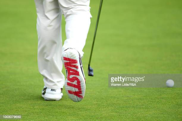 The golf shoes of Rory McIlroy of Northern Ireland seen as he putts on the 14th green during round three of the Open Championship at Carnoustie Golf...