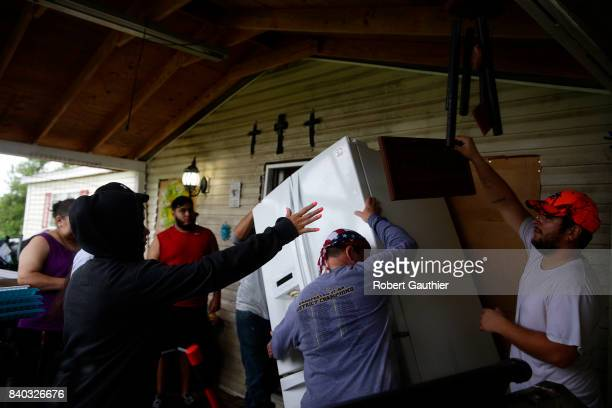 The Gonzalez family struggles to pack a refrigerator as they prepare to evacuate their home on the banks of the Brazos River