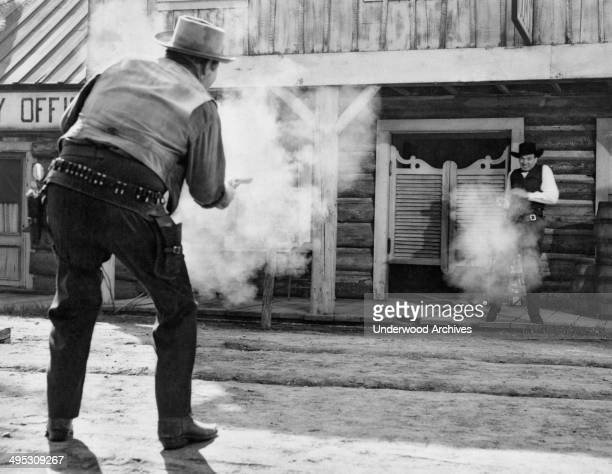 The good cowboy appears to get the draw on the bad cowboy in front of the saloon doors in this Western movie scene, Hollywood, California, circa 1950.