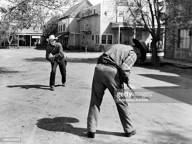 The good cowboy gets the draw on the bad cowboy and shoots the gun out of his hand in this Western movie scene Hollywood California circa 1950