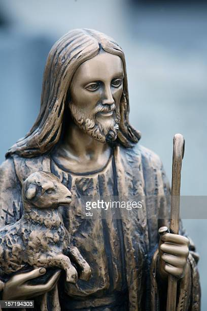 the good shepherd: golden jesus statue with lamb on arms - jesus the good shepherd stock pictures, royalty-free photos & images