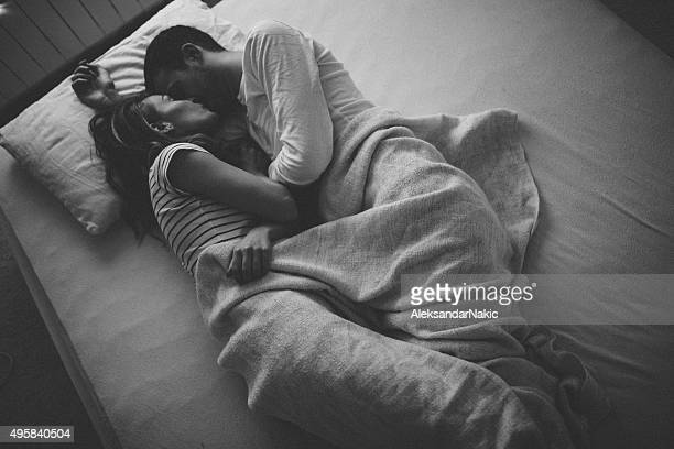the goodnight kiss - romantic young couple sleeping in bed stock photos and pictures
