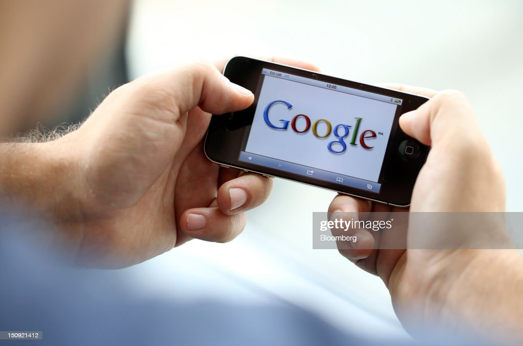 The Google Inc. company logo is seen on an Apple Inc. iPhone 4 smartphone in this arranged photograph in London, U.K., on Wednesday, Aug. 29, 2012. Apple Inc. is seeking a U.S. sales ban on eight models of Samsung Electronics Co. smartphones and the extension of a preliminary ban on a tablet computer after winning a patent trial against the South Korean company. Photographer: Chris Ratcliffe/Bloomberg via Getty Images