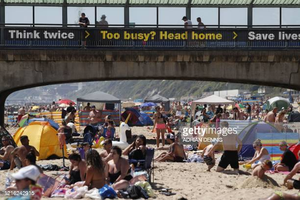 The government advice to stay home is seen written on the pier as sunbathers enjoy the sunny weather on Boscombe beach in Bournemouth southern...