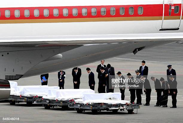 The government officials bow as the coffins of seven Japanese victims in the Dhaka terrorist attack arrive back on the special Japanese government...