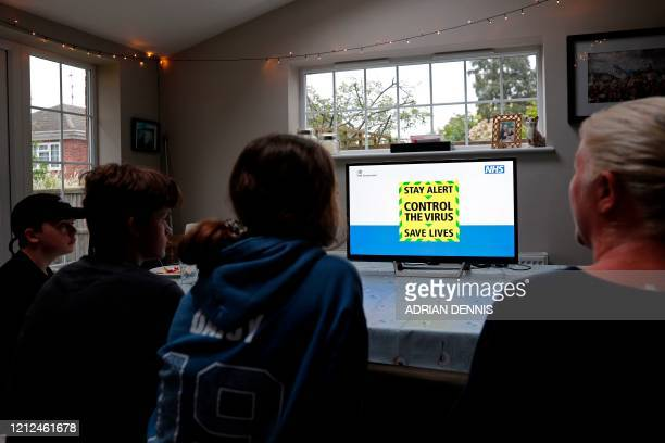 The government's new catchphrase is displayed on sceen as a family gather around the television to watch Britain's Prime Minister Boris Johnson give...