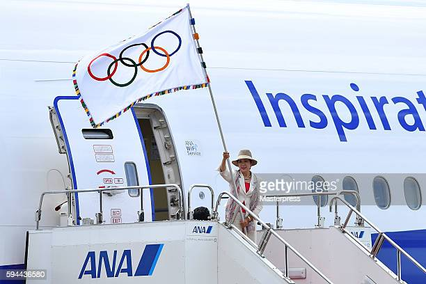 The governor of Tokyo Yuriko Koike walks out of an airplane with the Olympic flag during the 'The Arrival of Olympic Flag Ceremony' at the Haneda...