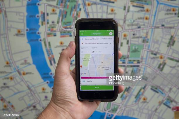 The Grab application is displayed on an Apple Inc iPhone in front of a map of Bangkok in an arranged photograph taken in Bangkok Thailand on Friday...