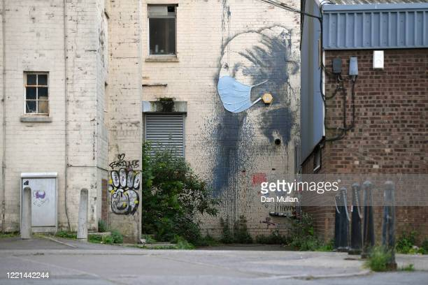 The graffiti artwork by Banksy named 'Girl with a Pierced Eardrum' is seen with a protective face mask at Hannover Place on April 27, 2020 in...