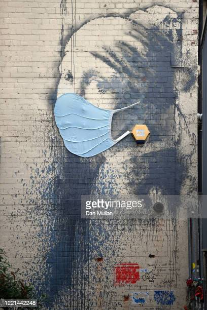 The graffiti artwork by Banksy named 'Girl with a Pierced Eardrum' is seen with a protective face mask at Hannover Place on April 27 2020 in Bristol...