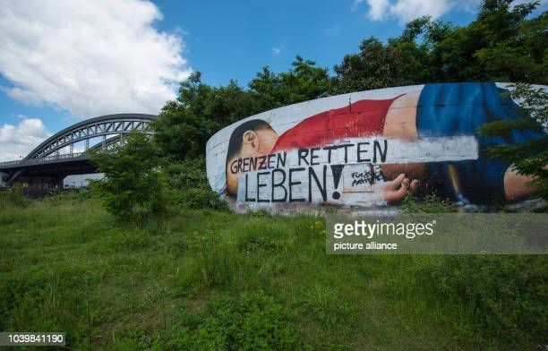 The Graffiti image of drowned Aylan has been painted over with the words 'Borders save lives' inFrankfurt am Main,Germany, 22 June 2016. In...