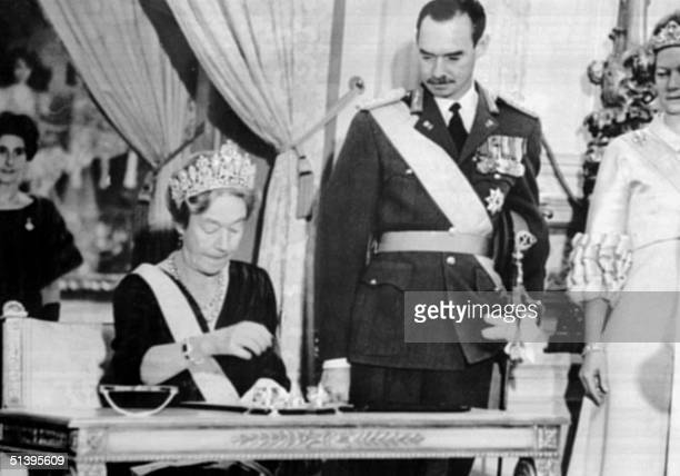 The Grand Duchess Charlotte of Luxembourg signs an abdication act 12 November 1964 in Luxembourg, as her son the Grand Duke Jean of Luxembourg looks...