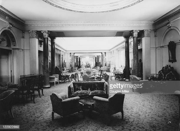 The Grand Hall and Lounge at new luxury hotel The Dorchester, decorated with light walls and red upholstery, Park Lane, London, 20th April 1931.