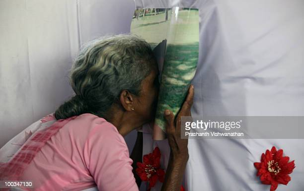The grand mother of an Air India Express crash victim mourns over the photograph on the coffin of her granddaughter H Goldine during a funeral...