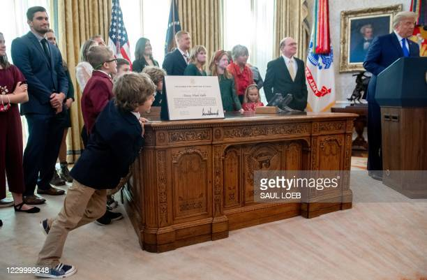 The grandchildren of wrestler Dan Gable lean against the Resolute Desk as US President Donald Trump speaks during a ceremony presenting the...