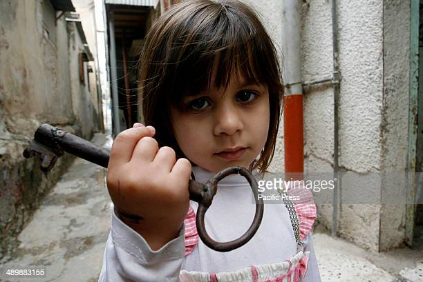 The granddaughter of Palestinian refugee, Subhia Abdul Rahim Abu Ghali, 79 years old, from the Rafah refugee camp holds up a key allegedly from her...