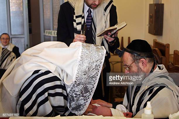 The grandfather of the baby boy assist the Mohel in holding the boy while the father of the boy reads a prayer before giving the Mohel the blade On...
