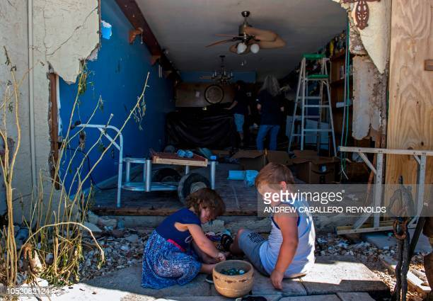 TOPSHOT The grandkids of Alethea Densmore play as she tries to salvage belongings in her apartment with family members in Port St Joe beach Florida...