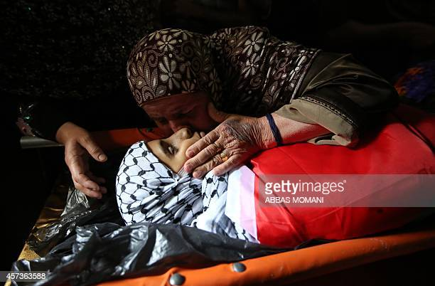 The grandmother of 13year old Palestinian teenager Bahaa Samir Badir mourns over his body during his funeral procession in the West Bank village of...