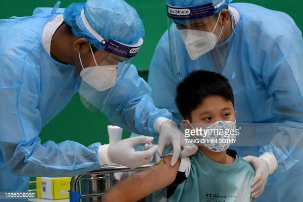 The grandson of Cambodia's Prime Minister Hun Sen receives a dose of the Sinovac Covid-19 coronavirus vaccine at the Peace Palace in Phnom Penh on...