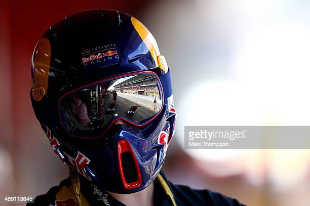 The grandstand and pit lane are reflected in the goggles of a member of the Infiniti Red Bull Racing team during qualifying ahead of the Spanish F1...