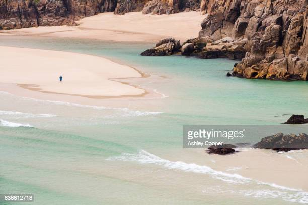 The Granite cliffs of Porthcurno with sandy beaches mid tide.